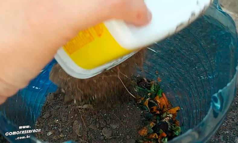 cobrindo os vegetais com terra na composteira de pobre