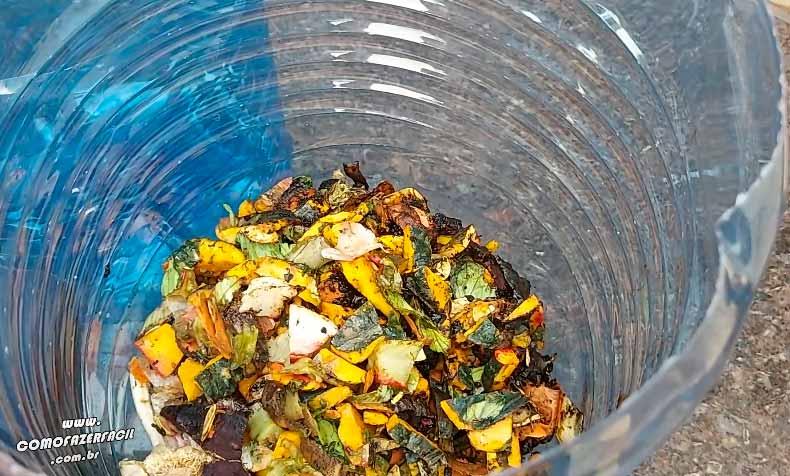 colocando camada de vegetais para se decompor na composteira