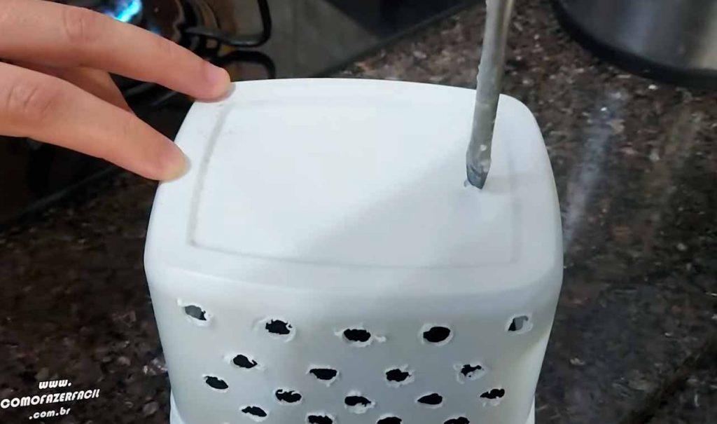 furando pote de margarina e sorvete para fazer porta talheres